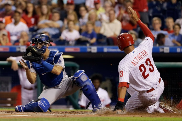 The Phillies' Aaron Altherr right, scores past Dodgers catcher Austin Barnes on a double by Tommy Joseph during the second inning of Wednesday's game in Philadelphia. Altherr has a home run in each of the first three games in this series and nine RBI. (AP Photo/Matt Slocum)
