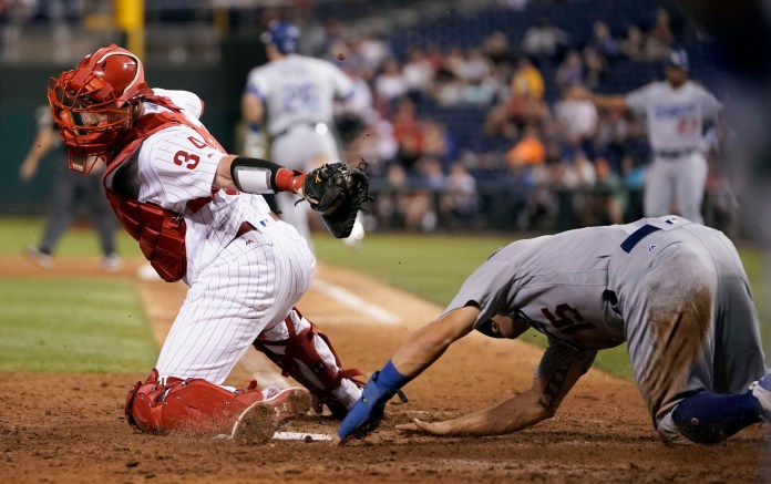 Philadelphia Phillies catcher Andrew Knapp, left, cannot reach Los Angeles Dodgers' Austin Barnes, who scored on a ball hit by Chase Utley during the eighth inning of a baseball game, Wednesday, Sept. 20, 2017, in Philadelphia. Philadelphia won 7-5. (AP Photo/Matt Slocum)