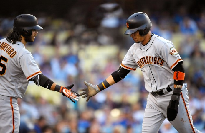 San Francisco Giants' Gorkys Hernandez, right, is congratulated by Brandon Crawford after scoring on a single by Buster Posey during the first inning of a baseball game against the Los Angeles Dodgers, Saturday, Sept. 23, 2017, in Los Angeles. (AP Photo/Mark J. Terrill)