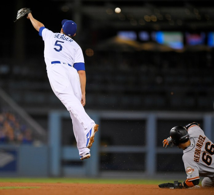 Los Angeles Dodgers shortstop Corey Seager, left, can't reach a ball thrown from home as San Francisco Giants' Gorkys Hernandez steals second during the fifth inning of a baseball game, Saturday, Sept. 23, 2017, in Los Angeles. (AP Photo/Mark J. Terrill)