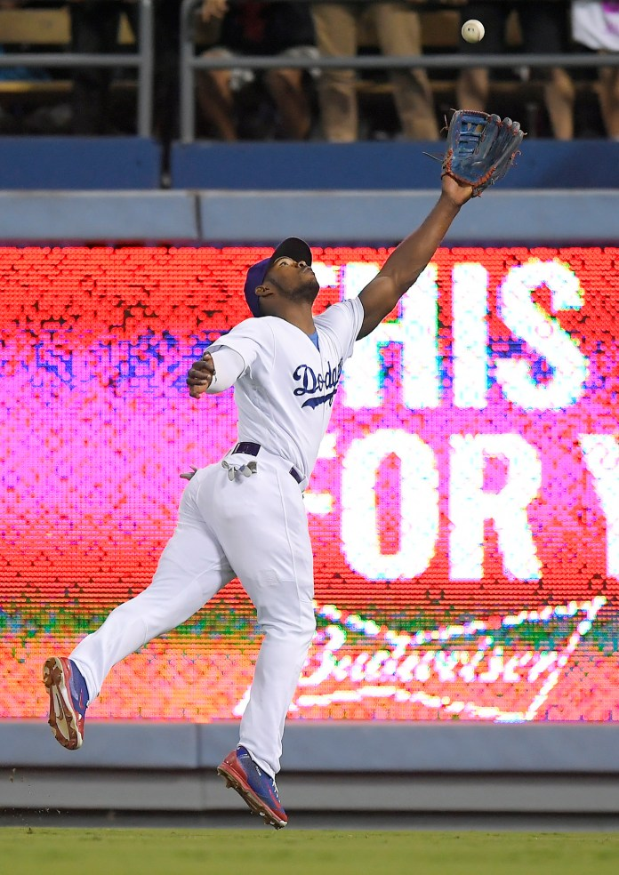 Los Angeles Dodgers right fielder Yasiel Puig can't handle a ball hit for a double by San Francisco Giants' Gorkys Hernandez during the seventh inning of a baseball game, Saturday, Sept. 23, 2017, in Los Angeles. (AP Photo/Mark J. Terrill)