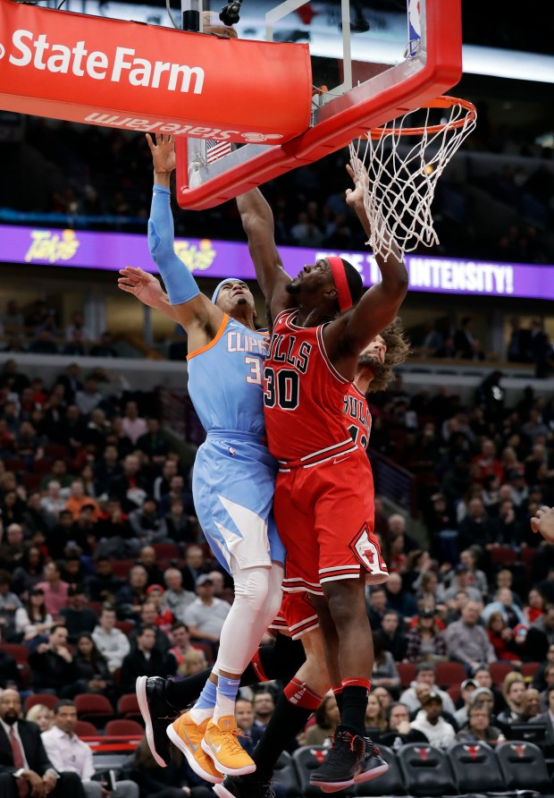 Chicago Bulls forward Noah Vonleh, right, blocks a shot by Los Angeles Clippers forward Tobias Harris during the first half of an NBA basketball game, Tuesday, March 13, 2018, in Chicago. (AP Photo/Nam Y. Huh)