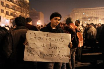 n Egyptian demonstrator demanding the ouster of Egyptian President Hosni Mubarak holds a placard asking tourists not to leave Egypt, on Cairo's Tahrir square on 1 February, 2011. (AFP / GETTY IMAGES / Miguel Medina)
