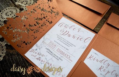 laser cut metallic copper invitation pocket with marble textured invite and rsvp inside