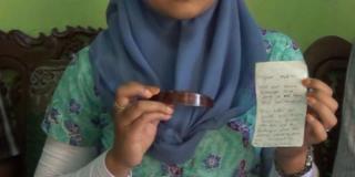 Nur Afrianan memperlihatkan penjepit rambut dan sepucuk surat yang diselundupkan sutinah dari penjara - Foto: kompas.com