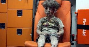 Bocah Suriah berusia 5 tahun, Omran Daqneesh, yang diselimuti debu dan darah, duduk di dalam ambulance setelah diselamatkan dari puing-puing reruntuhan bangunan yang terkena serangan udara Rusia di Aleppo pada 17 Agustus 2016. (Mahmoud Rslan / Getty Images)