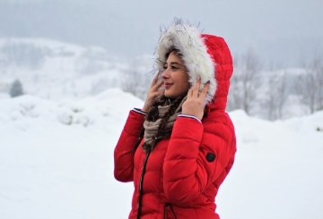 Joys of winter lady in red coat and hood