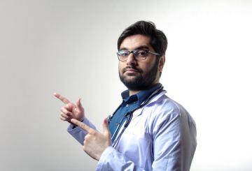 Doctor in white dress shirt wearing black framed eyeglasses