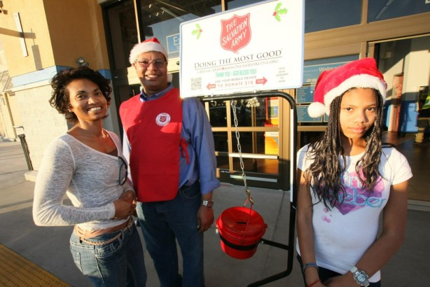 Salvation Army Board member Carl Dameron rings the bells with his family.  Left to right: Malaika, Carl and Shaila.  Photo by Ricard Tomboc