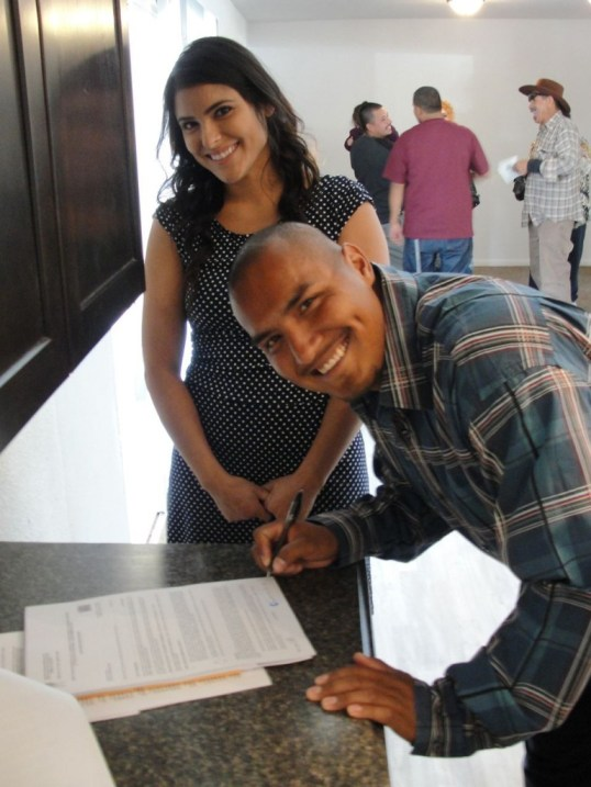 Steven and Jessica sign  the documents to their new house.