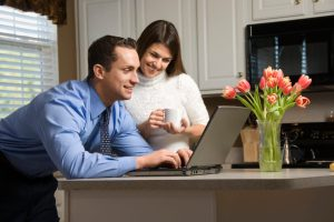 Caucasian couple in kitchen with coffee looking at laptop computer.