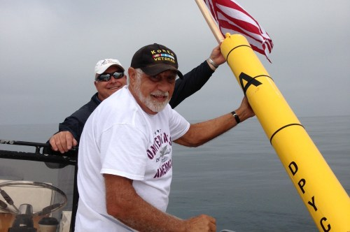 Chris Anastasio (right) and David Bolton replace a lost flag on a race marker just off the Dana Point coast. Photo by Barbara Merriman