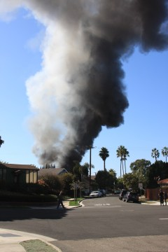 Smoke billows from a Capistrano Beach home November 5. Witnesses reported hearing a loud blast before the house on Vista Del Mar became engulfed in flames. Photo by Andrea Papagianis