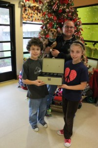 Aidan, 8 (left), and Madeleine Heller, 10, present Jennifer Stinett, shelter supervisor of the San Clemente-Dana Point Animal Shelter with a donation they raised collecting cans around their Dana Point neighborhood. Photo by Andrea Papagianis