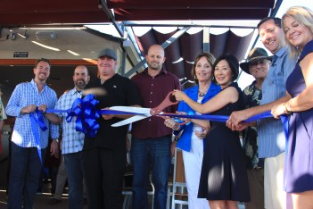 Waterman's Harbor owner Damian Collins (wearing the hat) is joined by members of his team, city officials and Dana Point Chamber of Commerce representatives for a ribbon cutting on Saturday, Sept. 13. Photo: Andrea Swayne