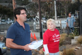 Dr. Nick Karahalios (San Clemente) speaks at the Ocean Institute on Monday, to a gathering of supporters of the current hospital facility while Carol Wilson (Capistrano Beach) photographs the event. Karahalios is holding thousands of petitions signed in support of keeping the hospital open. Photo: Jim Shilander