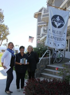 Suzie Kelley (center) the Shop Del Prado winner for March is presented with her prize package, including a one-night stay at the Blue Lantern Inn, by Chamber of Commerce Executive Director Heather Johnston (left) and Blue Lantern Inn General Manager Lin McMahon (right). Photo: Andrea Swayne