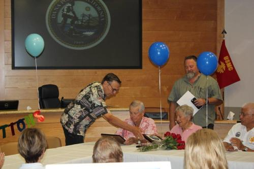 Mayor Carlos Olvera (left) presents Dick and Carol Ranger with plaques in honor of their service to VIPS as City Manager Doug Chotkevys (right, standing) looks on. Photo: B. Lohrman