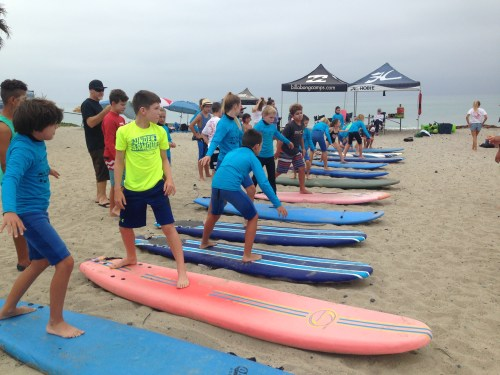 Cola's Surf Camp students practice pop-ups on the beach. Photo: Courtesy