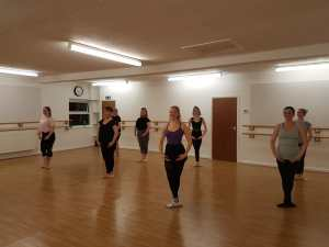 A group of young women stood in a starting position in an adult ballet class.