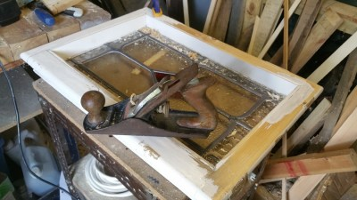 The first task is to prepare the window by restoring broken wood and stripping the old paint