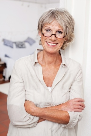 smiling older woman leaning against a door frame