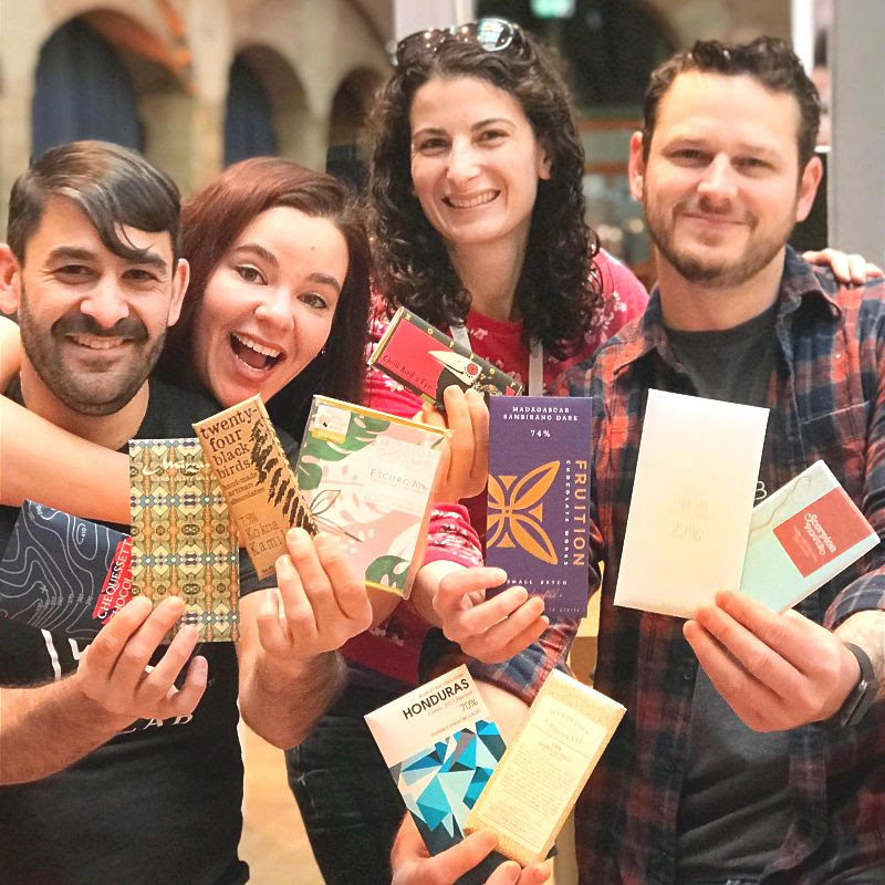 A group of chocolate makers holding chocolate bars