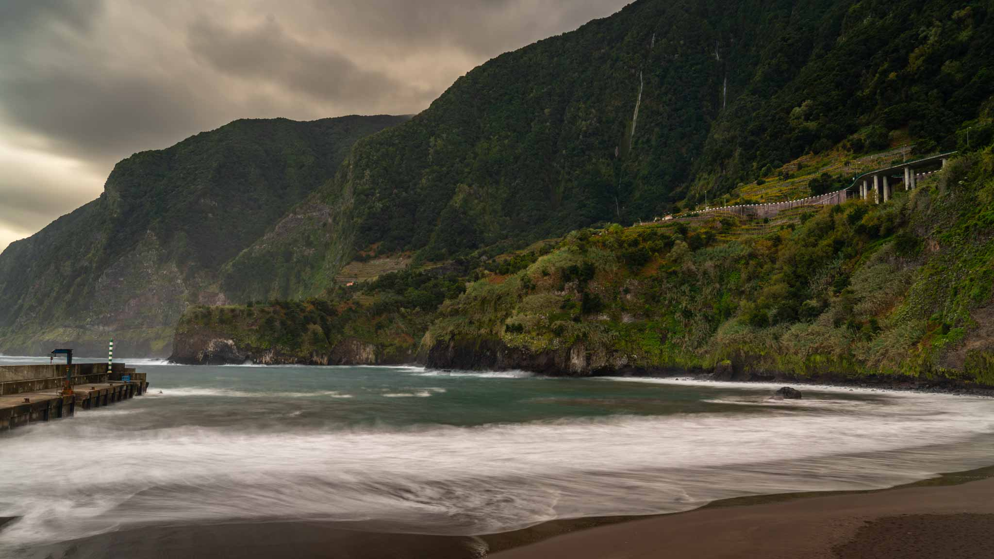 The black sand beach of Seixal with green cliffs and waterfalls