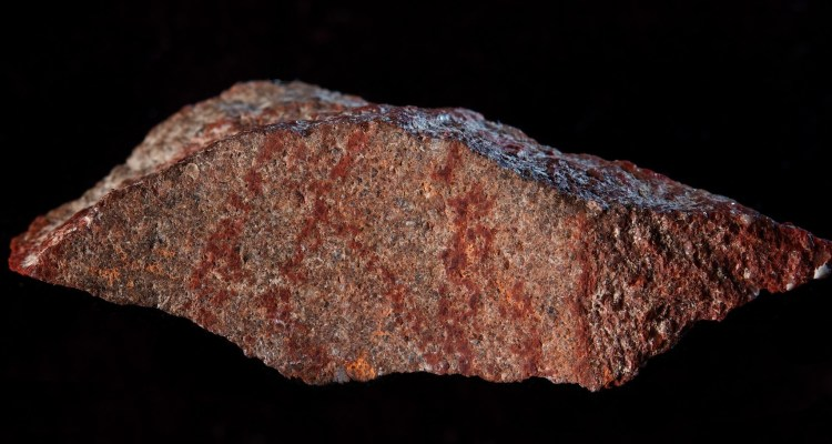 "A handout photo released on Setepmerb 12, 2018 by Nature Publishing Group shows the Blombos Cave drawing with ochre pencil on silcrete stone.   The earliest known drawing in history — a red, cross-hatched pattern — has been unearthed in South Africa, reports a study published online this week in Nature. Blombos Cave, located on the southern coast of South Africa, east of Cape Town, is a site that contains some of earliest known evidence of behaviourally modern human cultural activity. The cave has furnished an abundance of early human artefacts dated to between 70,000 and 100,000 years ago, including shell beads, engraved pieces of ochre and tools manufactured from pre-heated silicrete — a fine-grained cemented form of sand and gravel. / AFP PHOTO / NATURE PUBLISHING GROUP / Craig Foster / RESTRICTED TO EDITORIAL USE - MANDATORY CREDIT ""AFP PHOTO / NATURE PIBLISHING GROUP / CRAIG FOSTER"" - NO MARKETING NO ADVERTISING CAMPAIGNS - DISTRIBUTED AS A SERVICE TO CLIENTS"
