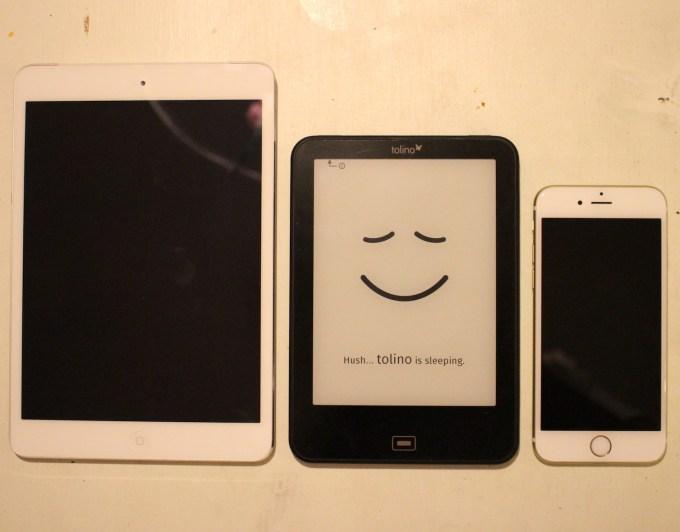 Tolino Vision 2 i storleksjämförelse med en iPad Mini 2 samt en iPhone 6S. Notera den diskreta lilla detaljen som talar om var man kan hitta på-knappen på Tolinon (eftersom skärmen är av e-bläckstyp stängs den aldrig helt av och blir svart i viloläget).