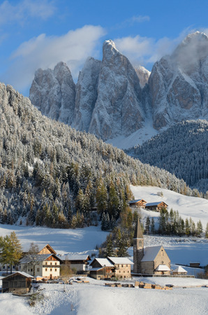 33419424 - the church of st. magdalena or santa maddalena, a village in front of the geisler or odle dolomites mountain peaks in the val di funes (villnösser tal) in south tyrol in italy in winter.