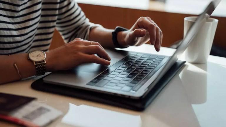 Pessoa utilizando laptop em cima de uma mesa