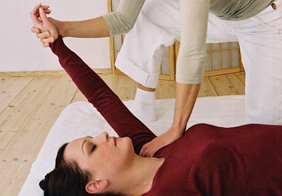 Frau wird behandelt. Therapeutin hält den Arm der am Boden liegenden Paitientin