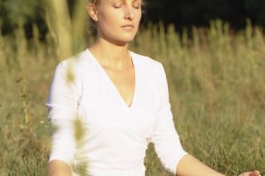 Sabine Barta meditiert, weißes Leibchen gegend die Sonne schauend
