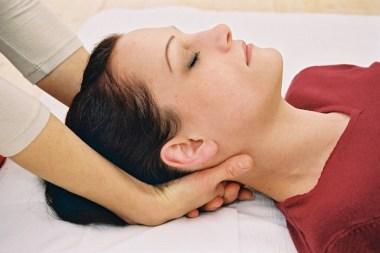 Therapeutin hält den Kopf, im Nacken, der liegenden Patientin, im DAO Zentrum