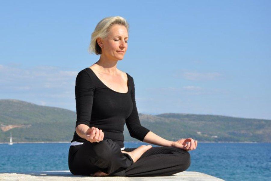 Sabine Barta meditierend am Strand mit blauem Himmel