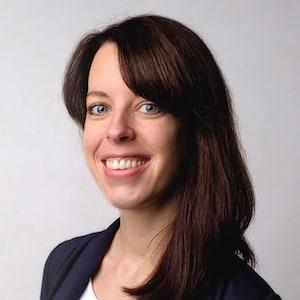 Martina Schneider lächelt. Sie trägt die schulterlangen, dunklen Haare offen.