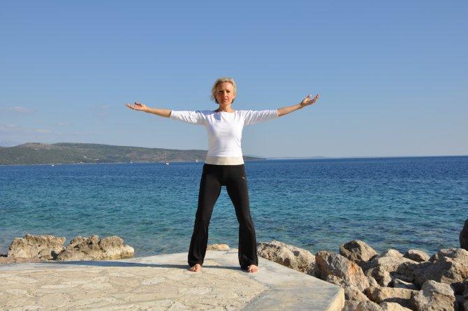 Sabine Barta bei Qigong Übungen am Meer, blauer Himmel
