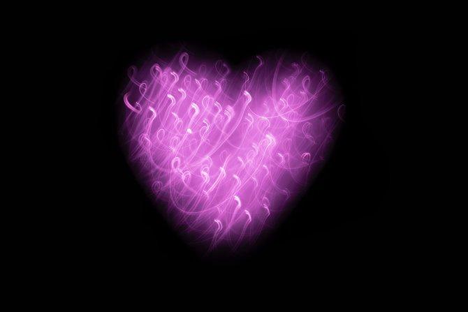 Herz aus lila Licht vor schwarzem Hintergrung