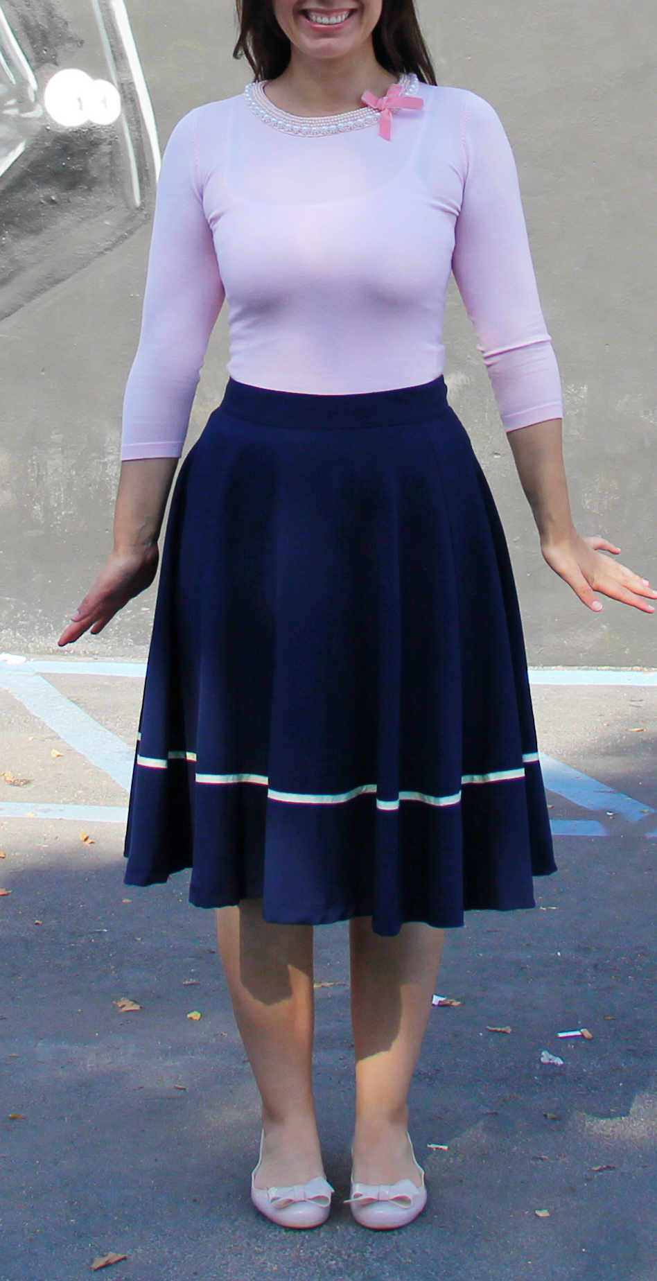 Pink sweater with neckline embellishment with navy midi skirt by Vader mural.