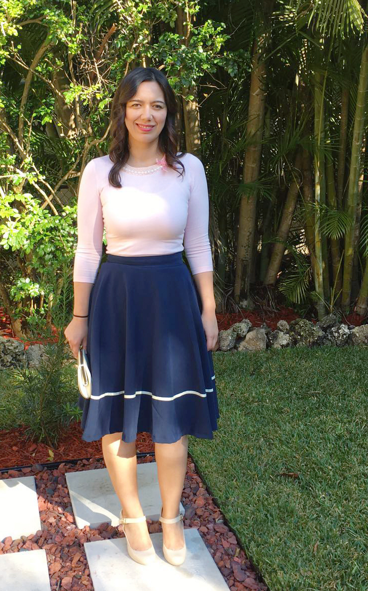 Pink sweater with neckline embellishment with navy midi skirt
