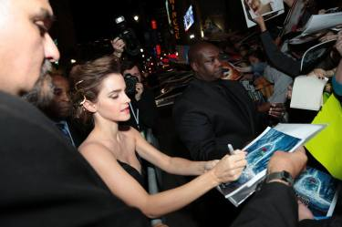 """Emma Watson signs autographs for fans during the world premiere of Disney's live-action """"Beauty and the Beast"""" at the El Capitan Theatre in Hollywood as the cast and filmmakers continue their worldwide publicity tour. (Photo: Alex J. Berliner/ABImages)"""