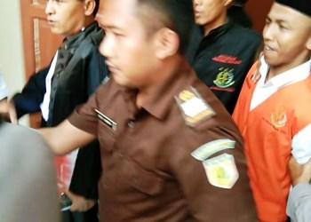 Jajang (rompi jingga) menebar senyum seusai vonis mati yang dijatuhkan majelis hakim Pengadilan Negeri Garut, Senin (14/10/2019). Foto: dara.co.id/Beni
