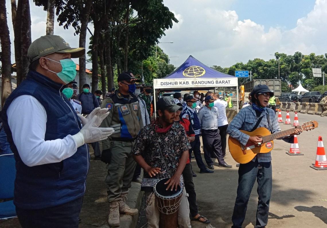 Bupati Bandung Barat, Aa Umbara Sutisna dihibur oleh sejumlah pengamen jalanan di sela meninjau titik pemeriksaan PSBB di GT Padalarang, KBB, Rabu (22/4/2020). (Foto: Heni Suhaeni/dara.co.id)