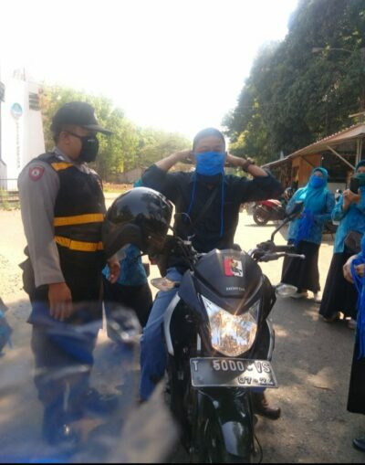 Semua pengguna jalan yang melintas ke Desa sadawarna diberi masker oleh jajaran kepolisian (Foto: Yudi/dara.co.id)