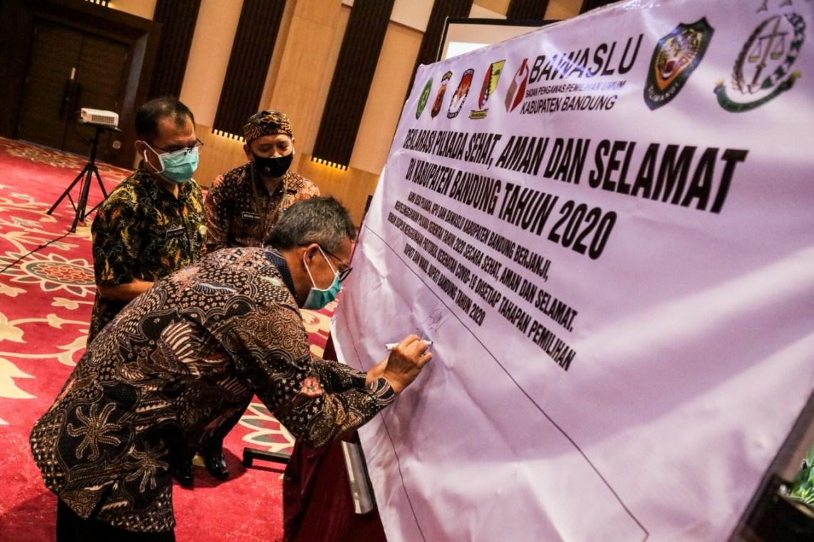 Pj Sekda Kabupaten Bandung, Tisna Umaran menandatangani pernyataan deklarasi Pilkada Damai pada acara Rakor Desk Pilkada di Grand Sunshine Hotel, Soreang, Kabupaten Bandung, Jawa Barat, Kamis (3/9/2020). (Foto: Humas Pemkab Bandung)