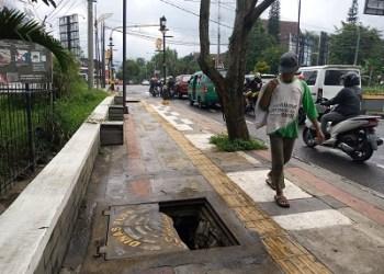 Seorang pejan kaki sempat menoleh kepada lubang yang menganga diatas trotoar di Jalan Raya Soreang, Kabupaten Bandung, Kamis (25/2/2021)