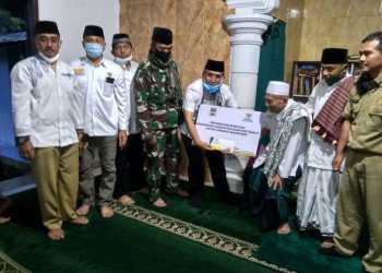 : Camat Cihampelas Jajang Nuryana Arifien menyerahkan bantuan ke Pimpinan Ponpes Nurul Hidayah, KH Hilman Yahya (Foto: Istimewa)
