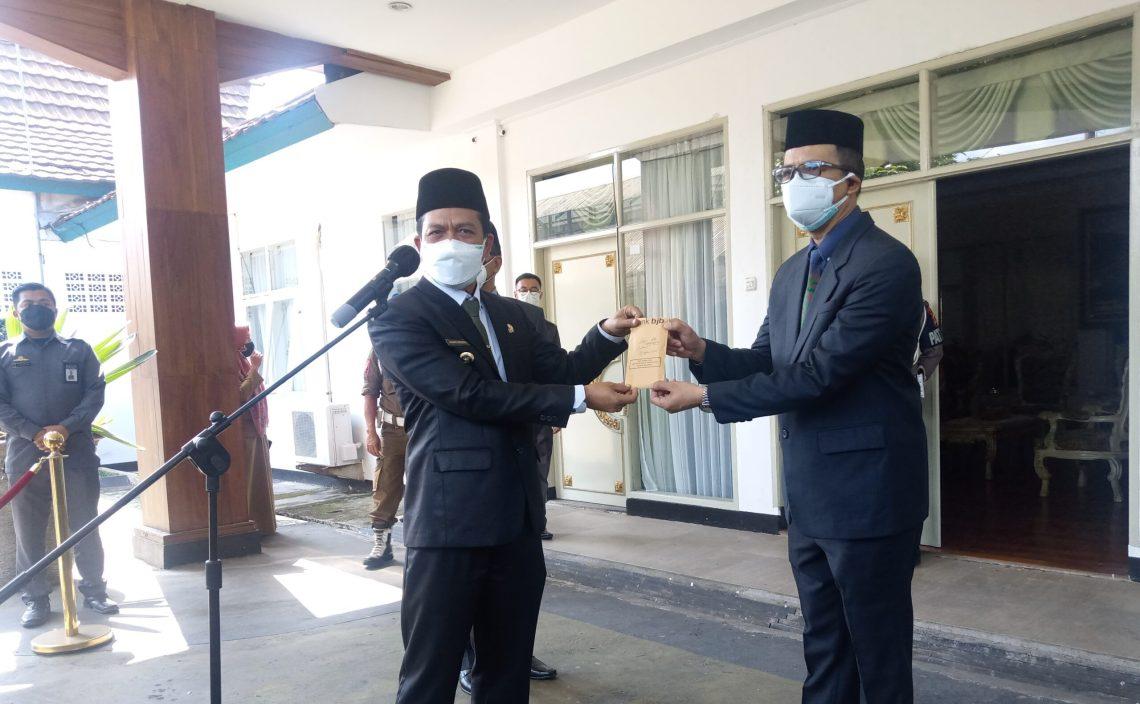 Bupati Bandung Dadang Supriatna menyerahkan gajinya bulan Agustus untuk membantu penanganan Covid-19 di wilayahnya. Amplop berisia uang gaji tersebut secara simbolis diserahkan kepada Sekda Cakra Amiyana di Rumah Dinas Bupati, Senin (2/8/2021). (Foto : Humas Pemkab Bandung)