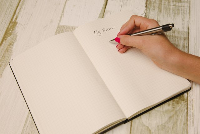 "An open notebook, with ""My Plan"" written at the top of a blank page, with a woman's hand holding a pen ready to write"